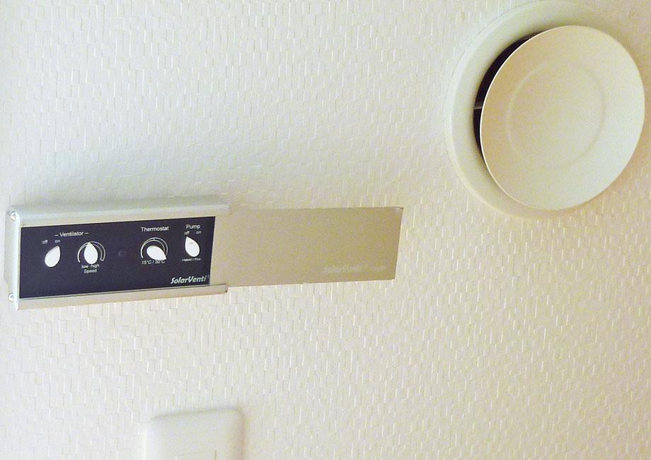 太陽熱で暖められた空気は右の給気口から室内に入る。左はコントローラーで、冷風を室内に入れないための設定などができる(写真提供;(株)マツナガ)